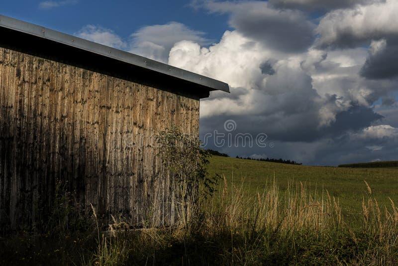 Hölzerne Scheune in einer Wiese unter Sturmwolken stockfotografie