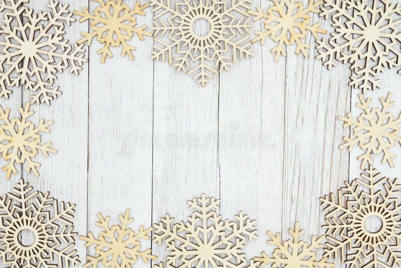 Hölzerne Schneeflocken auf verwittertem strukturiertem Holzhintergrund der Tünche lizenzfreies stockfoto