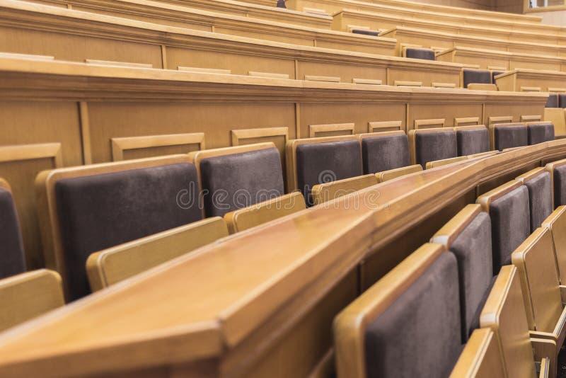 Hölzerne Schreibtische mit Stühlen im Vorlesungssal stockbilder