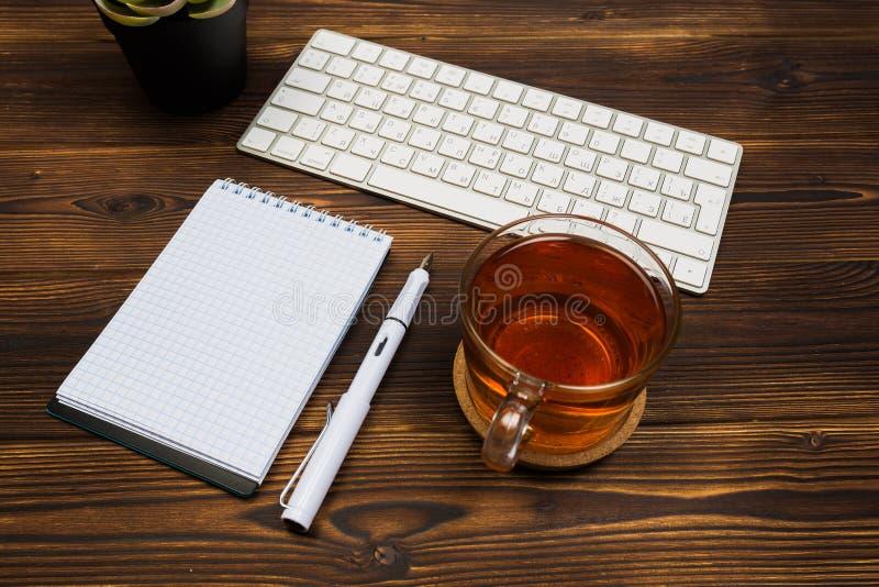 H?lzerne Schreibtischtabelle mit leerem Notizbuch und Versorgungen Draufsicht mit Kopienraum, flache Lage stockbild