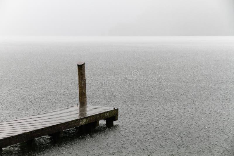 Hölzerne schwimmende Plattform als Brückenankern-Pierplattform auf einem alpinen See während des starken Regens mit niemandem stockfoto