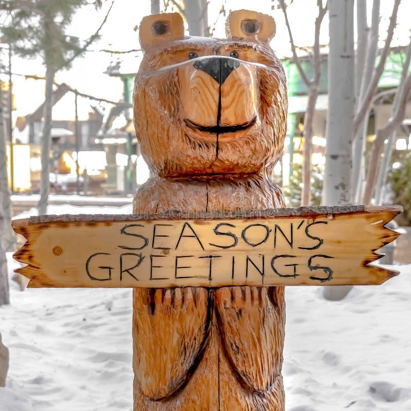Hölzerne Skulptur des quadratischen Bären auf einer Landschaft umfasst mit pulvrigem weißem Schnee im Winter stockbild