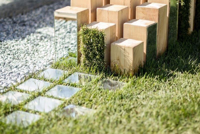 Hölzerne Skulptur mit Spiegeln auf dem Hintergrund des Grases Moderner Entwurf und Parkarchitektur vertikal lizenzfreie stockfotos