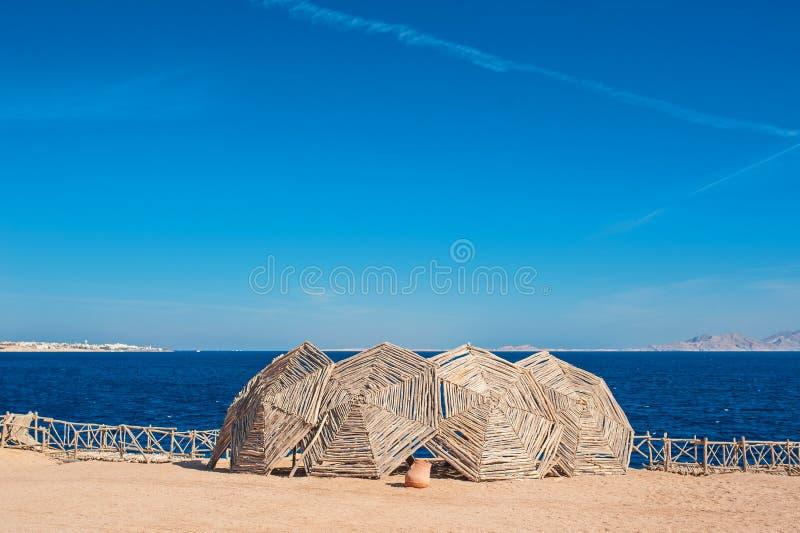 Hölzerne Sonnenschirme auf dem Strand stockfoto