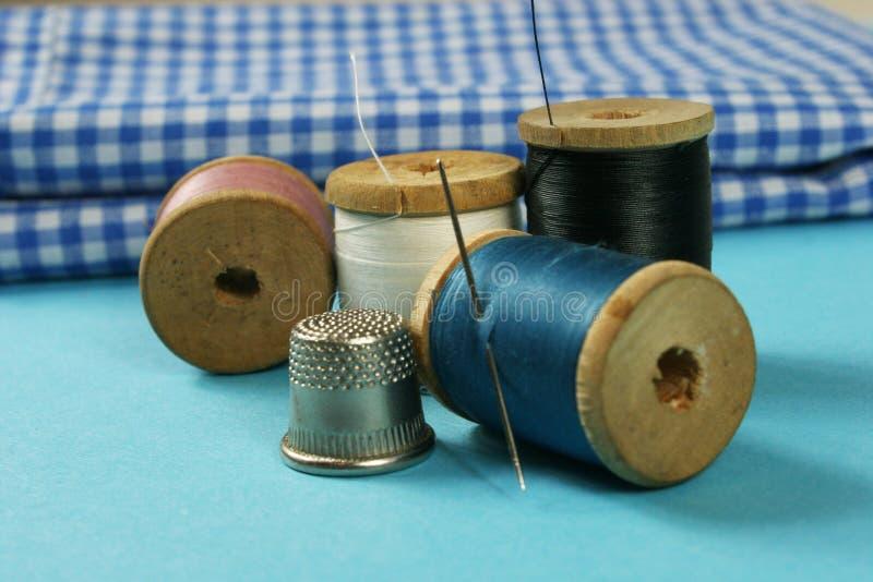 Hölzerne Spulen mit farbiger Baumwolle verlegt für das Nähen, stockfoto