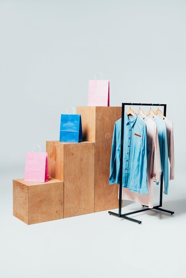 hölzerne Stände mit Einkaufstaschen und Stand mit Kleidung auf Weiß, Sommer lizenzfreie stockbilder