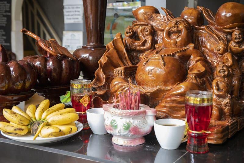 Hölzerne Statue des Lachens von Buddha mit duftenden Stöcken und Lebensmittelgeschenken Hölzerne schnitzende Kunststatue stockbilder