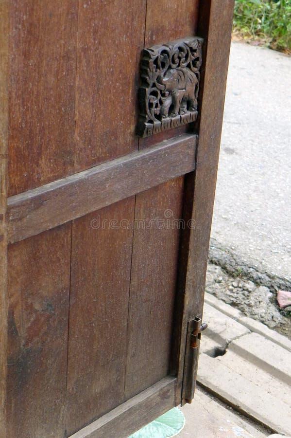 Hölzerne Tür des thailändischen Hauses, Elefantschnitzen lizenzfreie stockfotos