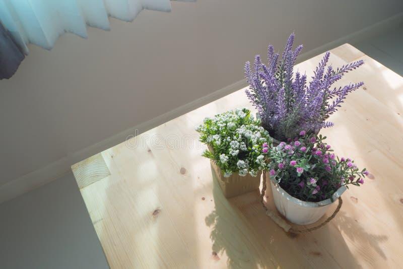 Hölzerne Tabelle mit Gruppe der schönen künstlichen Blume auf Topf an L lizenzfreies stockbild