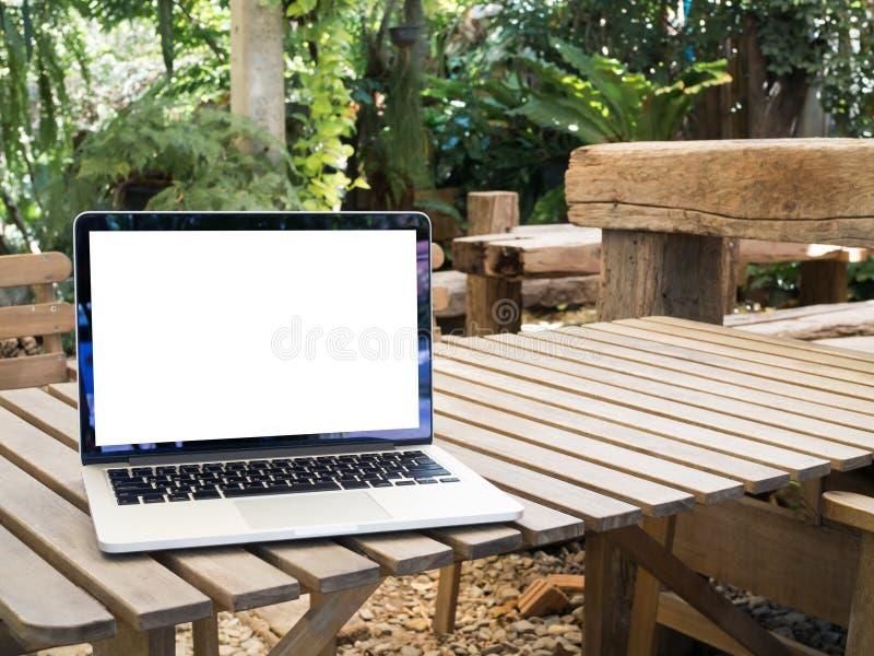 Hölzerne Tabelle mit leerem Bildschirm auf Laptop am Parkland lizenzfreies stockbild