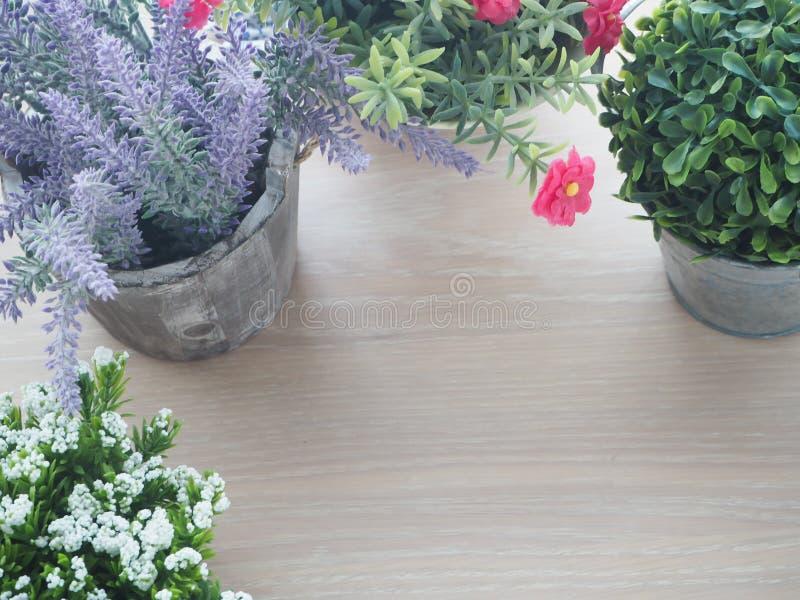 Hölzerne Tabelle mit schönem Blumenrahmen auf Topf und Freiexemplar spac stockfotografie