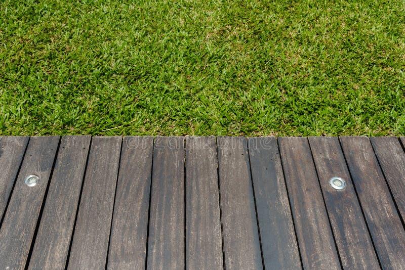 hölzerne Terrasse mit Beleuchtung und Grashintergrund stockfoto