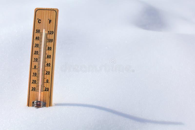 Hölzerne Thermometerstellung im Schnee, Sonne, die curvy shado wirft lizenzfreie stockbilder