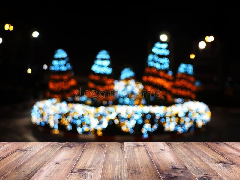 Hölzerne Tischplatte über undeutlichem Hintergrund der Weihnachtsbaum-Beleuchtungsdekoration auf Straße in der Stadt nachts Monta stockfoto