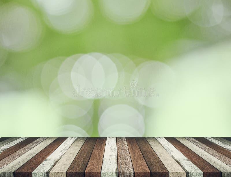 Hölzerne Tischplatte auf grünem bokeh Zusammenfassungshintergrund lizenzfreies stockfoto