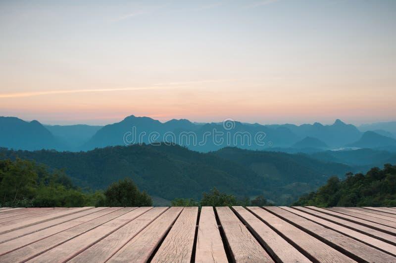 Hölzerne Tischplatte auf majestätischem Sonnenuntergang in den Bergen gestalten landschaftlich lizenzfreie stockbilder