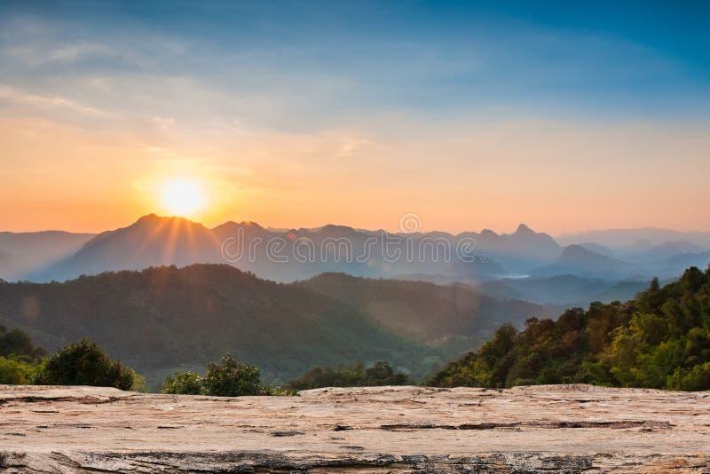 Hölzerne Tischplatte auf majestätischem Sonnenuntergang in den Bergen gestalten landschaftlich lizenzfreie stockfotos
