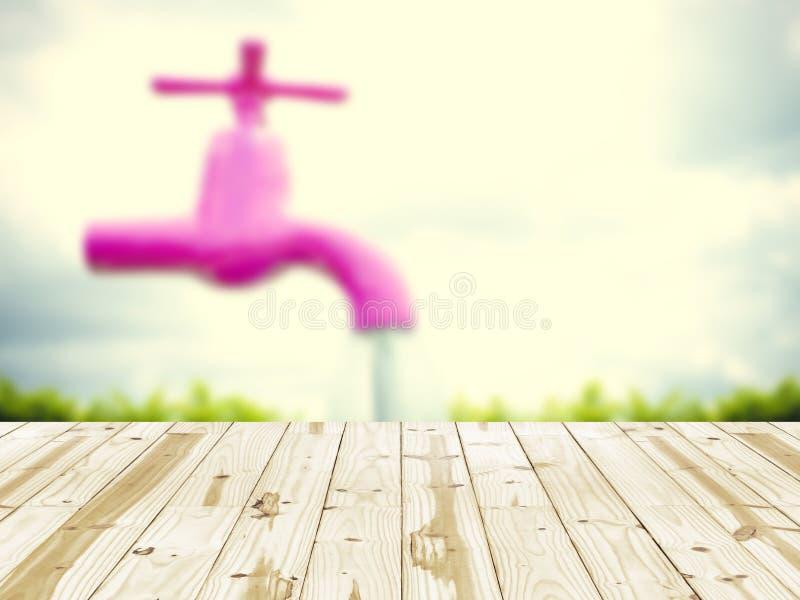 Hölzerne Tischplatte auf undeutlichen Hintergründen des rosa Hahns stockfotografie