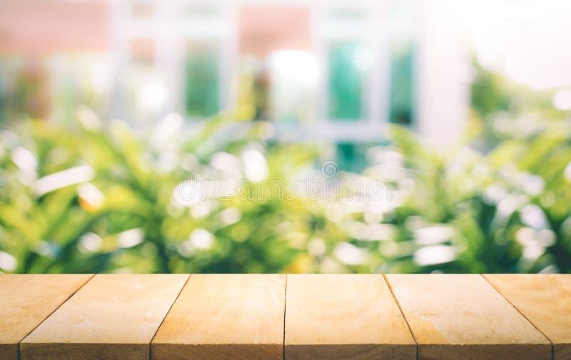 Hölzerne Tischplatte auf Unschärfe des Fensters mit Gartenblumenhintergrund lizenzfreie stockfotografie