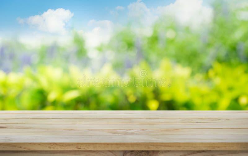 Hölzerne Tischplatte auf Unschärfebaum, Garten im Morgenhintergrund Seashells gestalten auf Sandhintergrund stockfoto