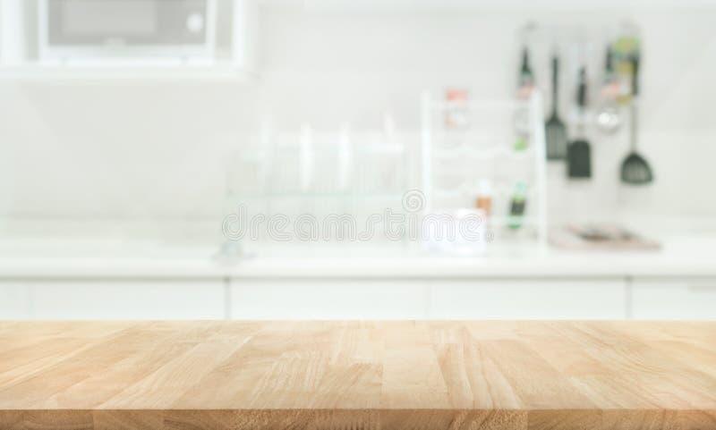 Hölzerne Tischplatte auf Unschärfeküchen-Raumhintergrund lizenzfreie stockfotos