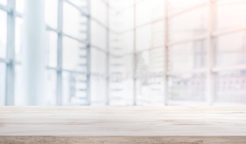 Hölzerne Tischplatte auf Unschärfeweißem Glasfensterhintergrundformbüro stockfotografie