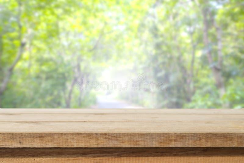 Hölzerne Tischplatte auf Unschärfezusammenfassungsgrün vom Garten lizenzfreie stockfotos