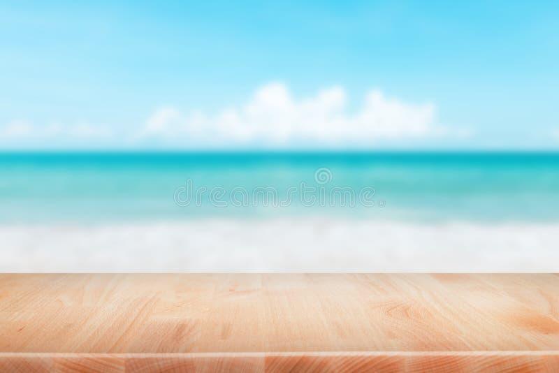 Hölzerne Tischplatte auf unscharfem blauem Meer und weißem Sandstrand backgrou stockbild