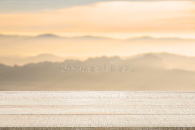 Hölzerne Tischplatte auf unscharfer Berglandschaft stockbild