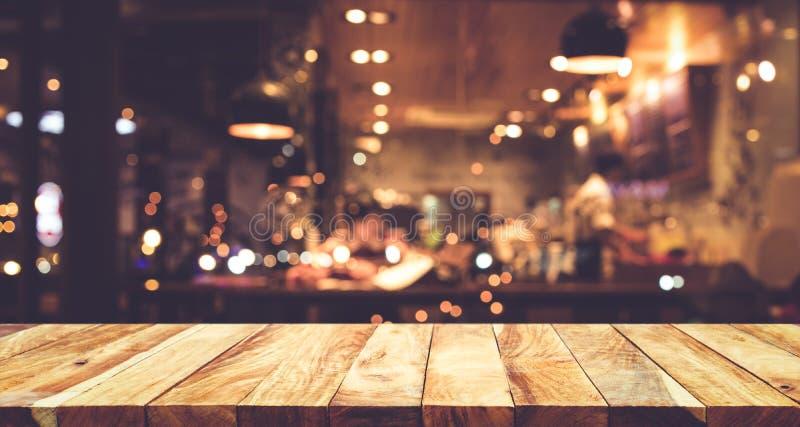 Hölzerne Tischplatte Bar mit Unschärfenachtcaféhintergrund