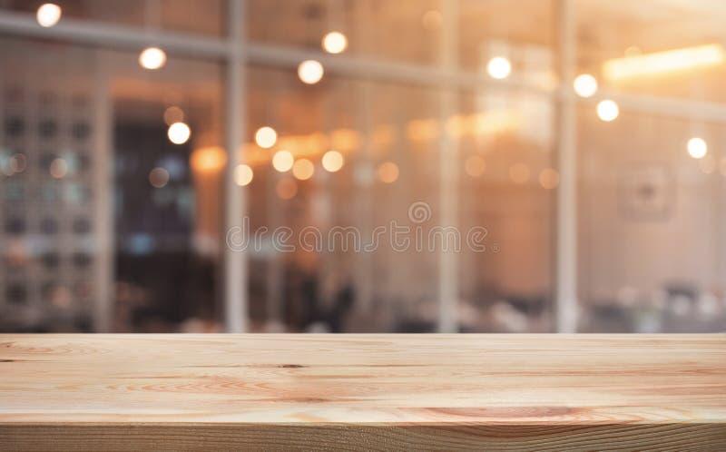 Hölzerne Tischplatte mit hellem Goldcafé, Restauranthintergrund stockfotos