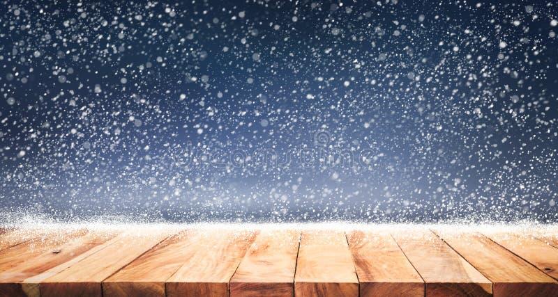 Hölzerne Tischplatte mit Schneefällen des Wintersaisonhintergrundes Weihnachten stockfotos