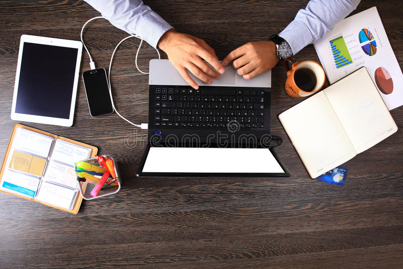 Hölzerne Tischplattendraufsicht des Weinlesehippies, männliche Hände unter Verwendung des Laptops stockbilder