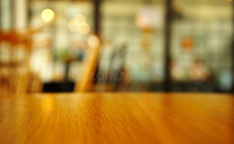 Hölzerne Tischplatteoberfläche mit Unschärfecafé-Innenraumhintergrund lizenzfreies stockbild