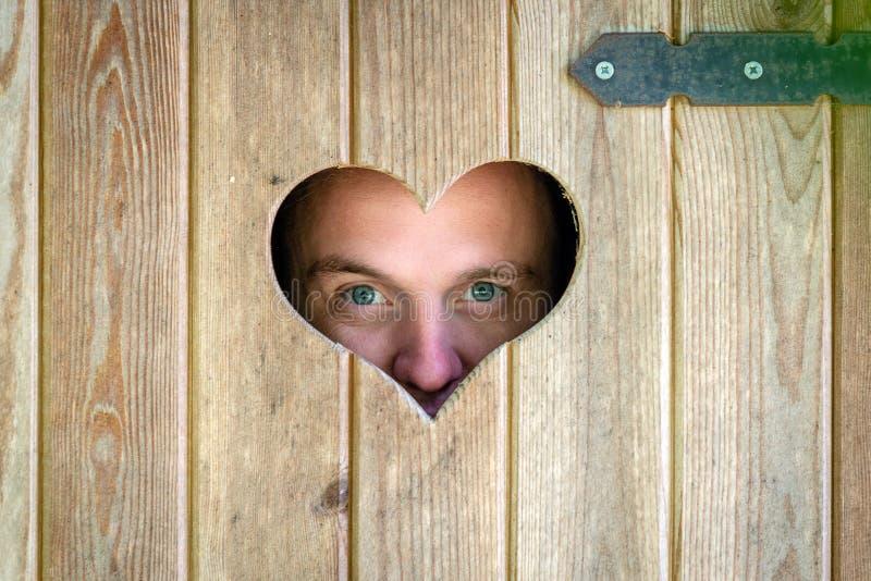 Hölzerne Toilette im Freien mit Herzen auf der Tür Ein Mann geht durch ein Herz-förmiges Fenster lizenzfreie stockfotos