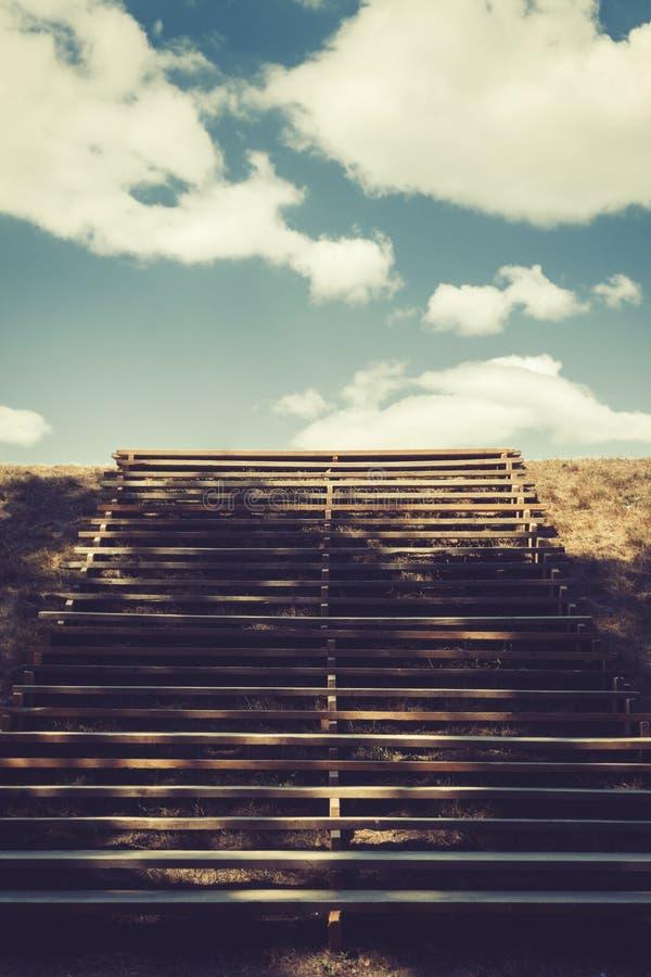 Hölzerne Treppe, die zum blauen Himmel mit weißen Wolken führt stockbilder