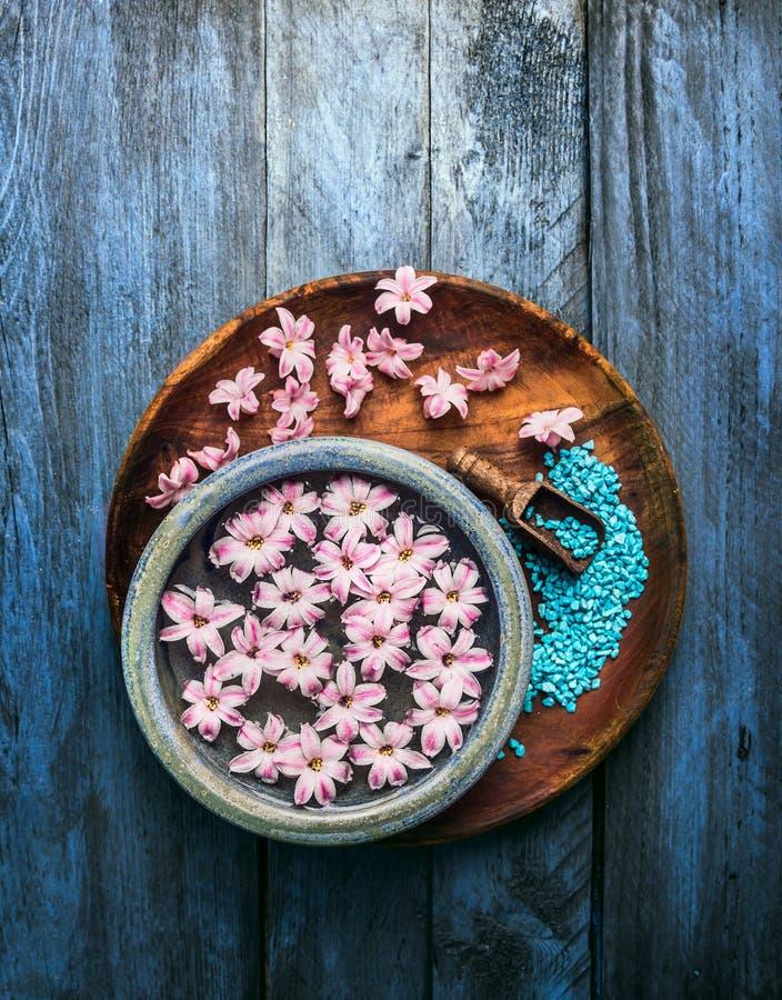 Hölzerne und blaue Schüssel mit rosa Blumen und Wasser, Schaufel mit Seesalz auf altem Hintergrund stockbilder