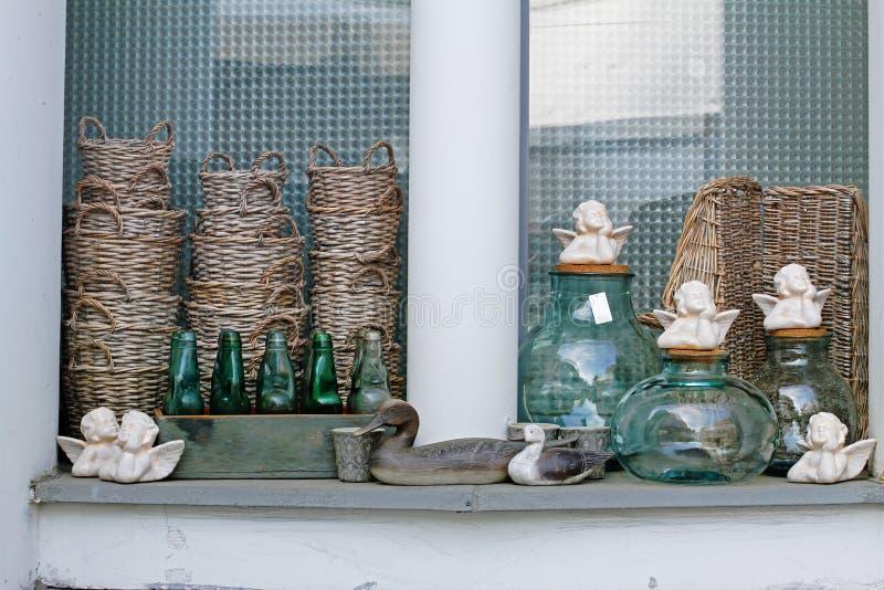 Hölzerne Vögel, Weidenkörbe, keramische Engel, Blumentöpfe, Glasflaschen und Gläser in den Blumenladen lizenzfreie stockfotografie