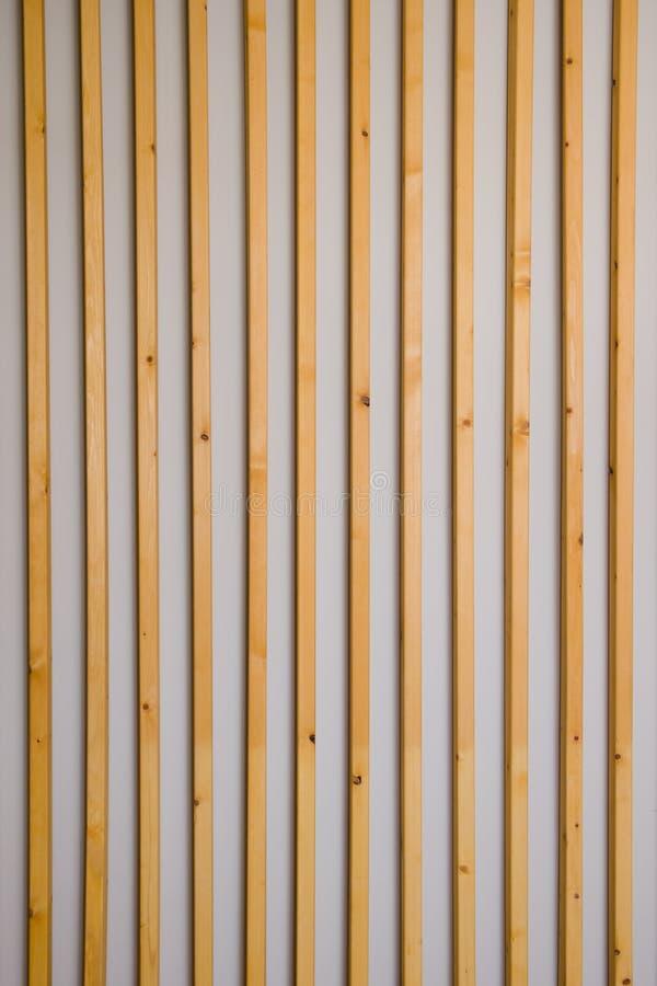 Hölzerne vertikale Latten batten auf einem hellgrauen Wandhintergrund Innendetail, Beschaffenheit, Hintergrund Das Konzept des Mi stockbilder