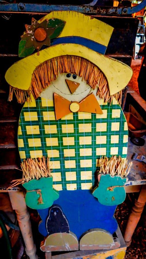 Hölzerne Vogelscheuche mit gelbem Hut stockbilder
