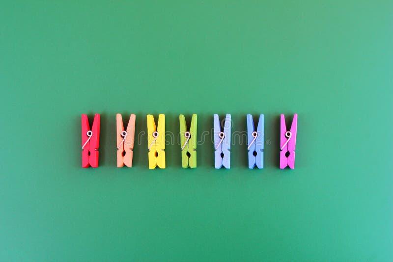 Hölzerne Wäscheklammerregenbogenfarben werden in Folge auf einem grünen Hintergrund vereinbart lizenzfreies stockbild