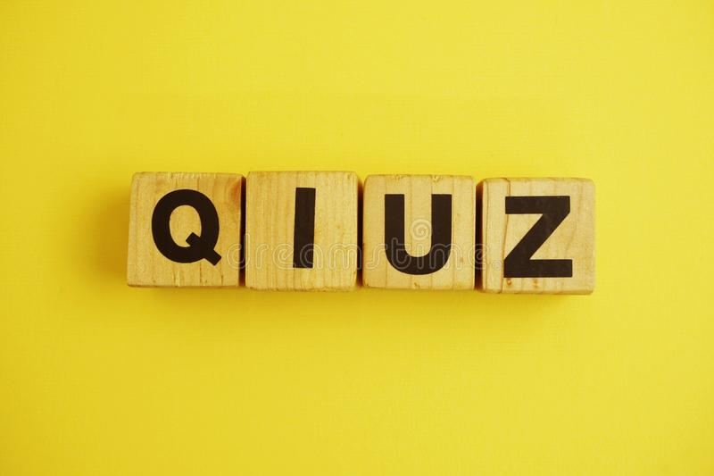 Hölzerne Würfel des Quizbuchstabe-Alphabetes auf gelbem Hintergrund lizenzfreies stockbild