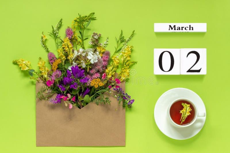 Hölzerne Würfel tragen am 2. März ein Schale Krauttee, Kraftpapier-Umschlag mit multi farbigen Blumen auf grünem Hintergrund Konz stockfotografie