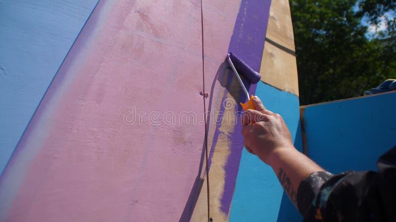 Hölzerne Wand der weiblichen Handfarbe in der blauen Farbe unter Verwendung der Malereirolle Malen des Holzes mit weißem Farbenro stockfotografie