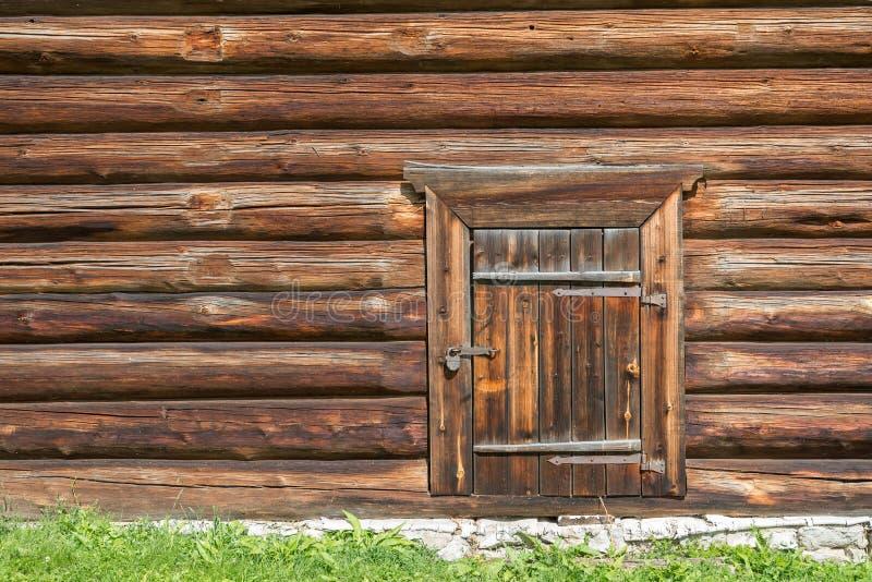 Hölzerne Wand des alten Blockhauses mit geschlossener Tür und Vorhängeschloß auf ihm stockfoto