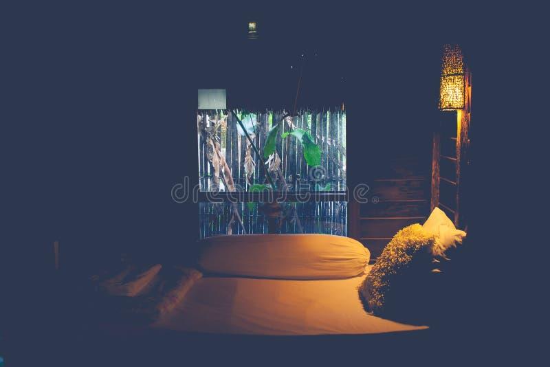 Hölzerne Wandlampe der Weinlese, die auf hölzerner Wand über dem Bett im Schlafzimmer hängt stockbild