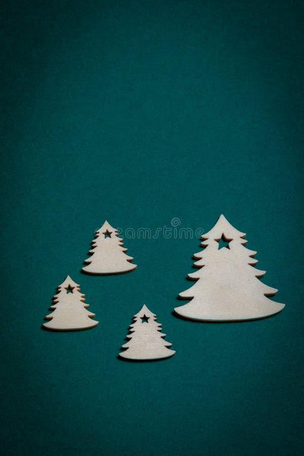 Hölzerne Weihnachtsbäume auf Weihnachtsgrünem Hintergrund stockfotos