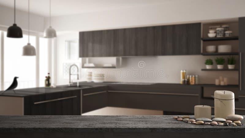 Hölzerne Weinlesetischplatte oder -regal mit Kerzen und Kieseln, Zenstimmung, über unscharfer moderner minimalistic Küche, graue  lizenzfreie stockfotos