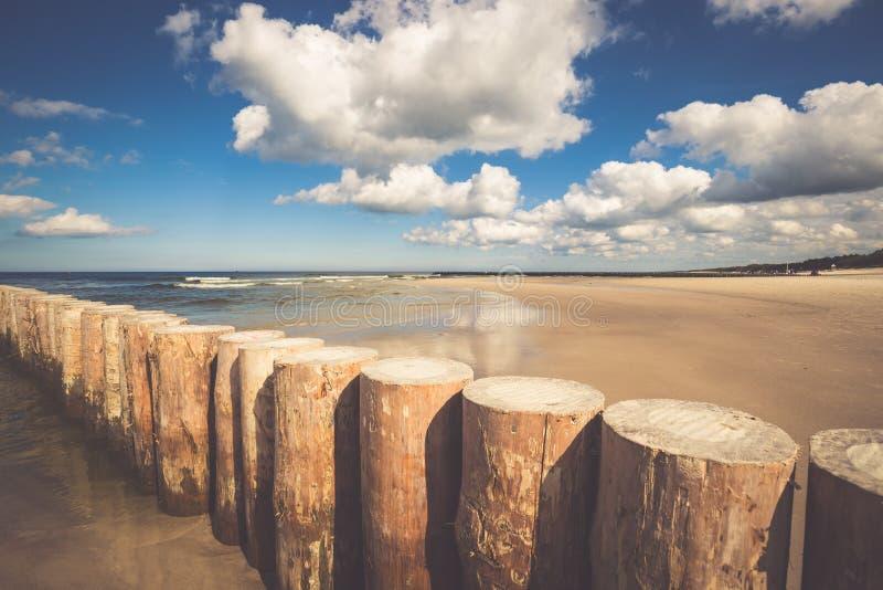 Hölzerne Wellenbrecher auf sandigem Leba setzen am späten Nachmittag auf den Strand, baltisch stockfotografie
