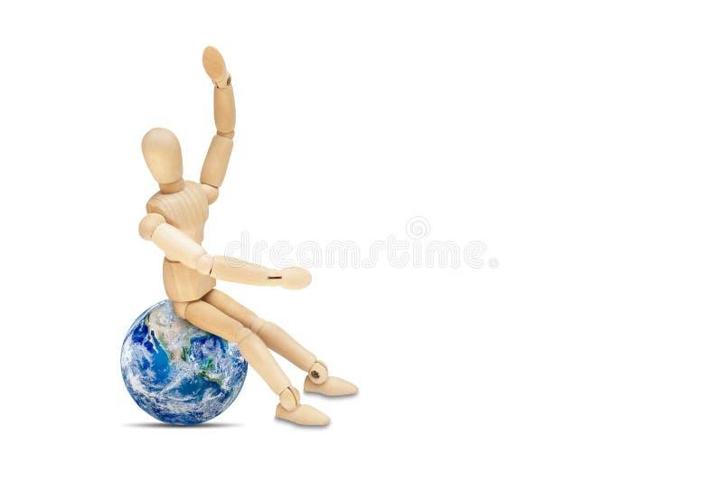 Hölzerne Zahl Mannequin, das auf der Planetenerdkugel lokalisiert auf weißem Hintergrund sitzt stockfotografie